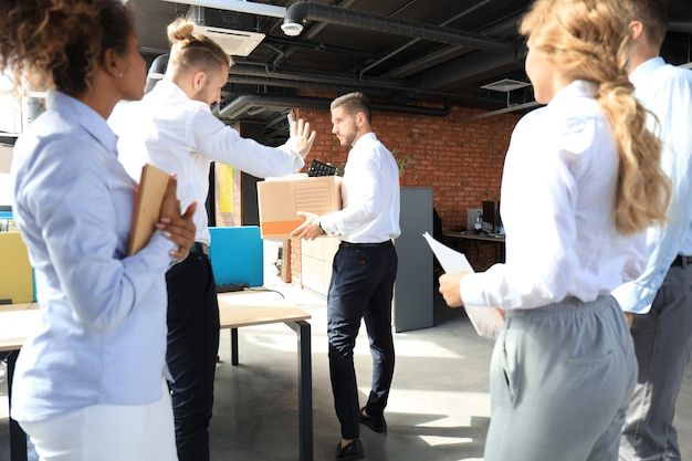 Коллеги по бизнесу провожают уволенного сотрудника из офиса.