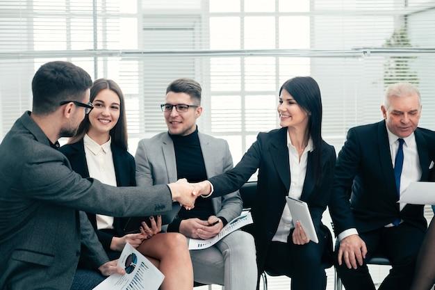 Коллеги по бизнесу приветствуют друг друга в конференц-зале. концепция сотрудничества