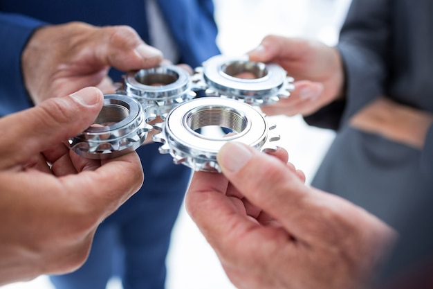 Business colleagues holding cog