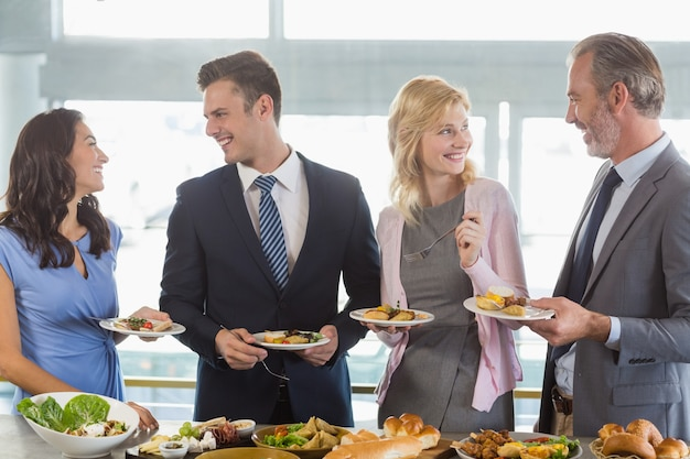 Business colleagues interacting while serving themselves at buffet lunch