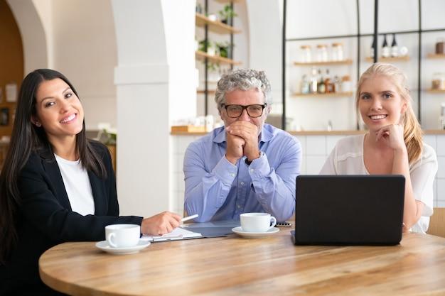 Деловые коллеги или партнеры разного возраста встречаются за чашкой кофе в коворкинге, сидя за столом с ноутбуком и документами,