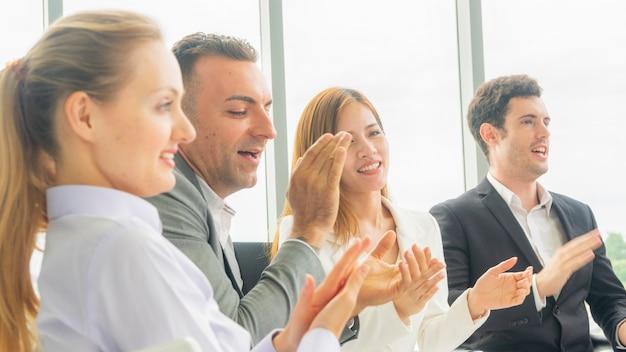비즈니스 동료 사람들이 여자 박수 및 회의실에서 회의 듣고 앉아.