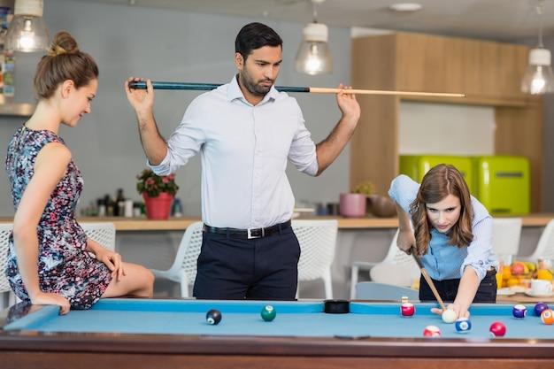 Деловые коллеги играют в бильярд в офисном помещении