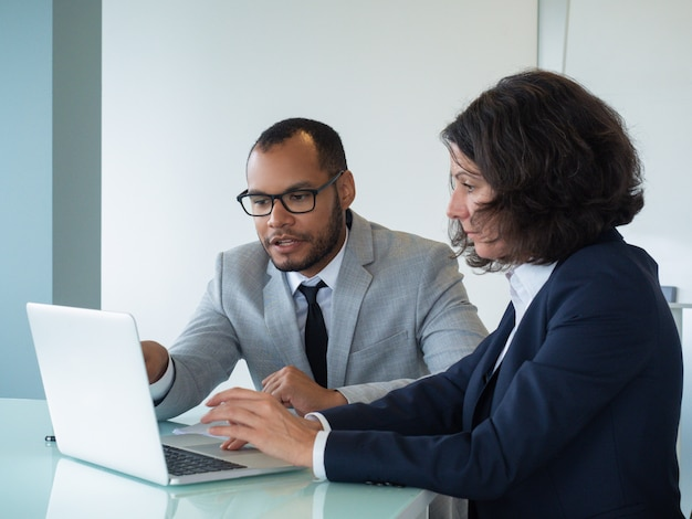 Бизнес коллеги рассматривают и обсуждают отчет