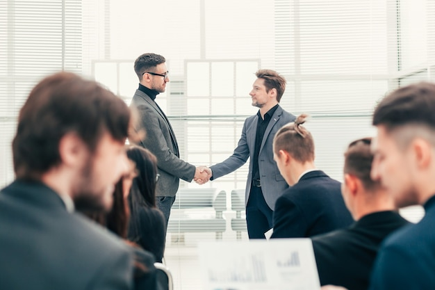 会議中に握手する同僚。成功の概念