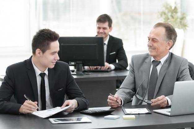 Коллеги по бизнесу, сидя за столом в офисе