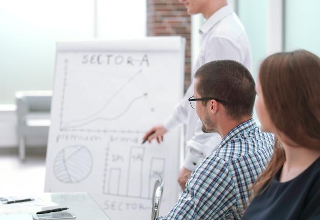 비즈니스 동료들은 책상에 앉아 새로운 아이디어에 대해 토론하고 복사 공간이 있는 사진을 토론합니다.