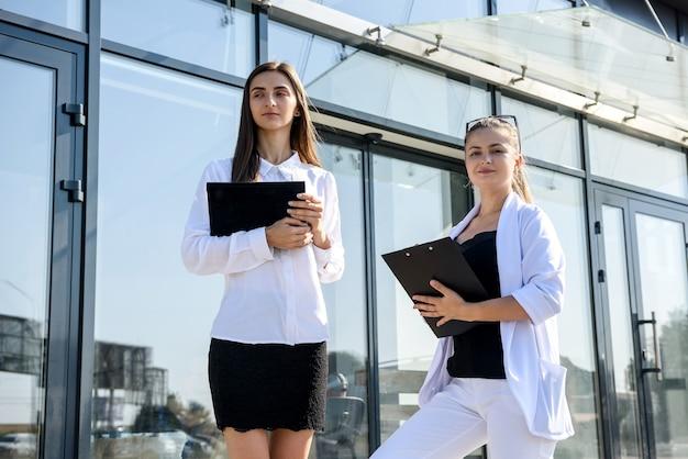 タブレットとクリップボードを使って大きなオフィス センターの前に立つビジネスの同僚