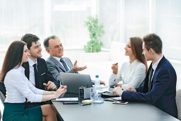 オフィスのデスクで話している同僚。チームワークの概念