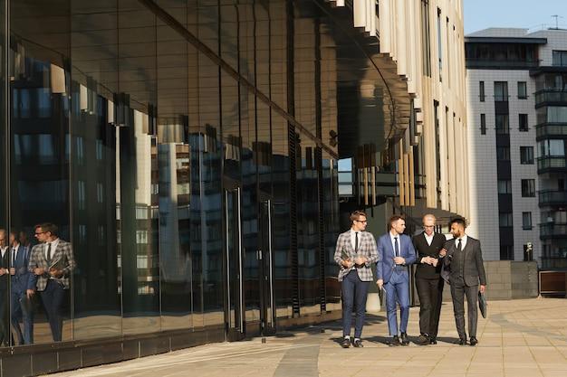 백그라운드에서 현대적인 건물로 도시에서 산책하는 동안 서로 이야기하는 비즈니스 동료