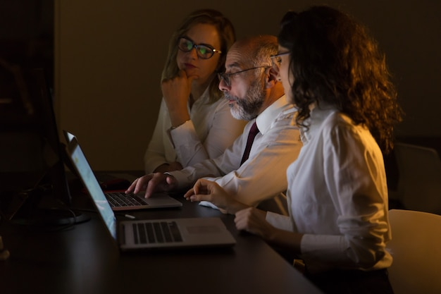 Business colleagues using laptops at night