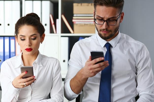 職場で最新のスマートフォンを使用しているビジネス部門の同僚