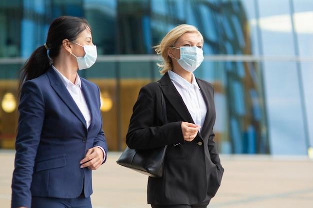 オフィススーツとマスクを身に着けているビジネス同僚、会議、市で一緒に歩く、話している、プロジェクトについて話し合っている。ミディアムショット。ビジネスとコロナウイルスのコンセプト