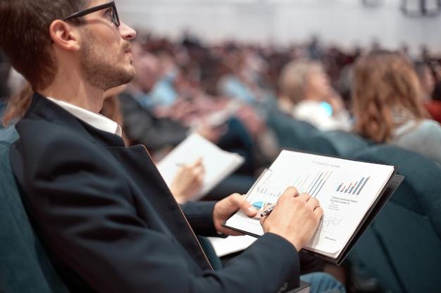 会議ホールに座っている財務スケジュールを持つ同僚