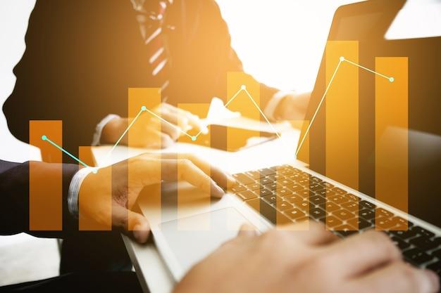 어두운 색조와 현대 직장에서 디지털 태블릿 및 노트북을 사용하는 비즈니스 동료