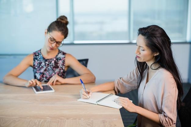 ビジネス部門の同僚がメモ帳で書いて、会議室でデジタルタブレットを使用