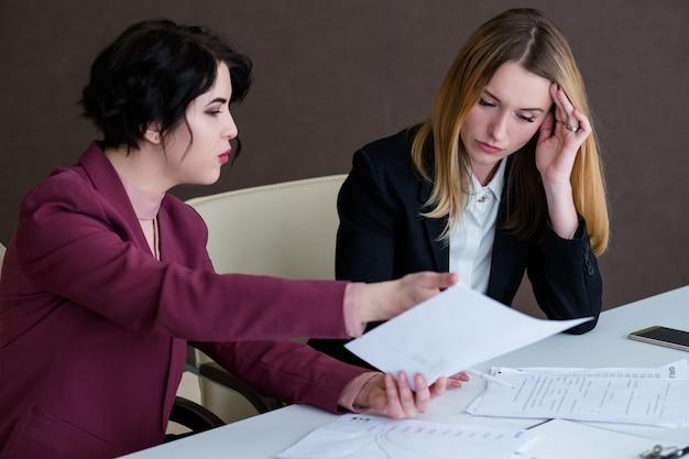 Деловое общение и объяснение. две женщины обсуждают документы в офисе