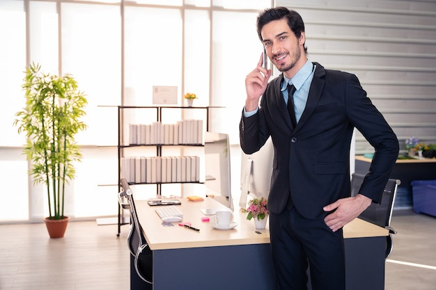 Business communication. businessman talking on phone standing in office