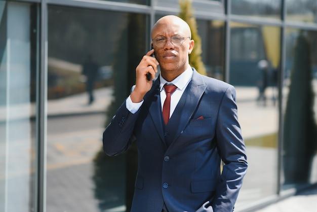 Деловое общение. веселый афро бизнесмен, разговаривая по телефону в центре города. копировать пространство