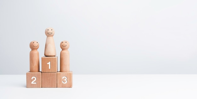 ビジネス競争の勝者。最初の賞の受賞者の表彰台に立っている幸せな女性、コピースペースと白い背景の上の木製の立方体ブロック上の木製の図。目標、成功、およびリーダーシップの概念。