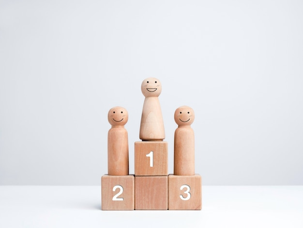 Business competition winner. smiling female standing on the winner podium on the first award, wooden figure on wood cube block on white background. women power, goals, success, and leadership concept.