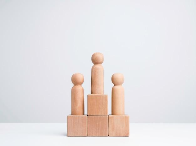 ビジネス競争の勝者。勝者の表彰台に立っている木製のフィギュア、コピースペース、最小限のスタイルで白い背景の上の木製の立方体ブロック。目標、成功、およびリーダーシップの概念。
