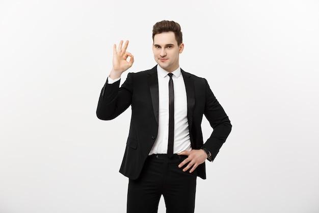 ビジネスコンセプト:okの兆候を示す灰色の背景に分離されたスマートスーツのハンサムな男。