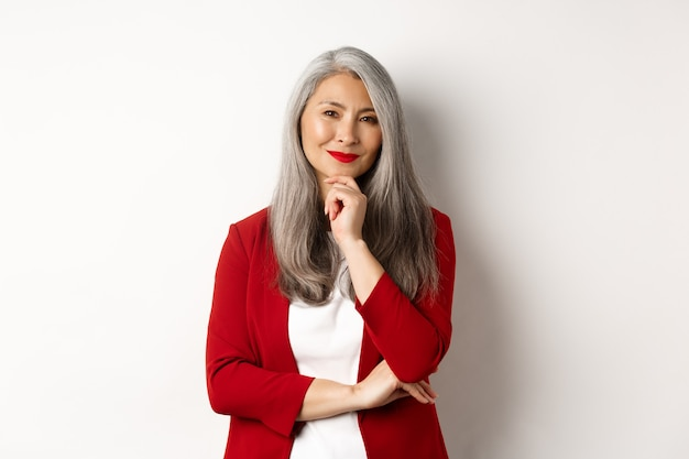 비즈니스 개념. 아시아 성숙한 사업가 기쁘게 웃 고, 사려 깊은 찾고, 아이디어, 흰색 배경 위에 빨간색 재킷에 서 서.