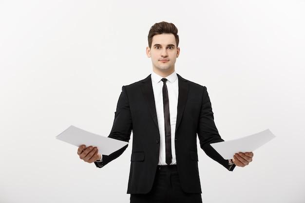 비즈니스 개념: 종이 보고서를 비교하는 세심한 잘생긴 사업가. 흰색 회색 배경 위에 절연.