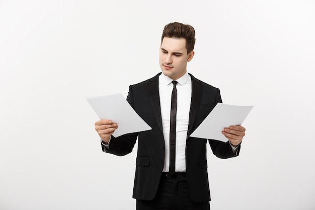 Business concept: attentive handsome businessman working comparing paper report. isolated over white grey background.