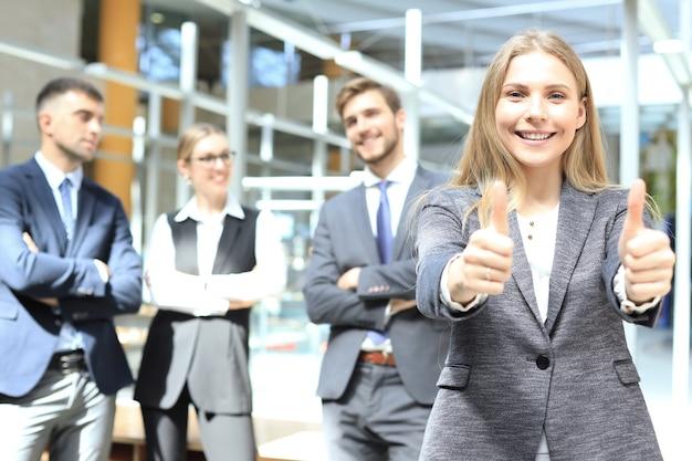 Бизнес-концепция - привлекательная бизнес-леди с командой в офисе показывает палец вверх.