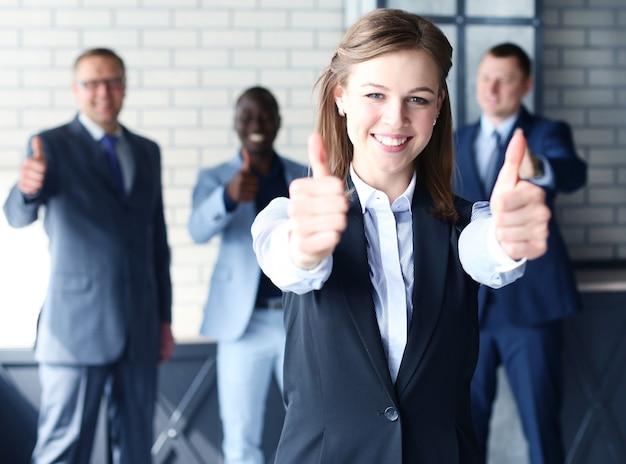 Бизнес-концепция - привлекательная бизнес-леди с командой в офисе показывает палец вверх