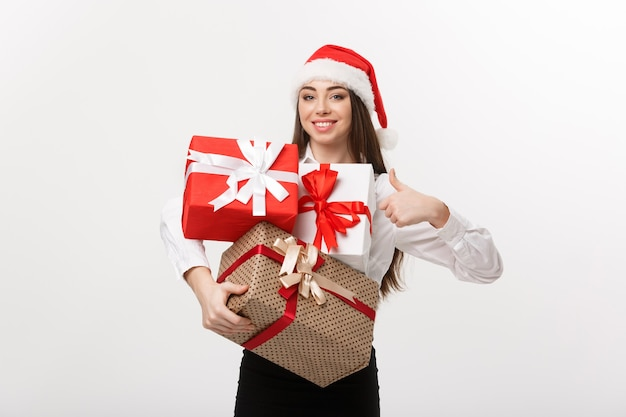 Business concept  beautiful young caucasian business woman with santa hat holding a lot of gift boxes and showing thump up