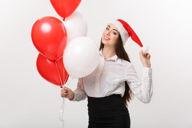 ビジネスコンセプト-風船を持ってサンタの帽子をかぶった美しい若い自信を持ってビジネス女性がクリスマスを祝います。