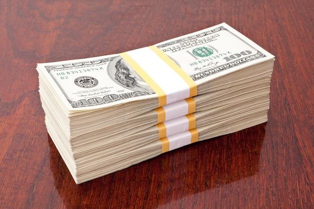 Бизнес-концепция. большая стопка денег за столом