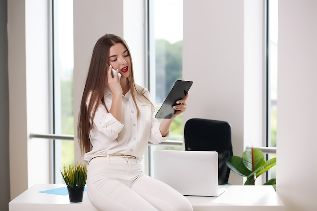 事業コンセプト-オフィスで電話で話しているブルネットの実業家