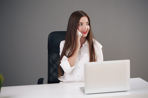 Business concept - brunette businesswoman talking on the phone in the office,
