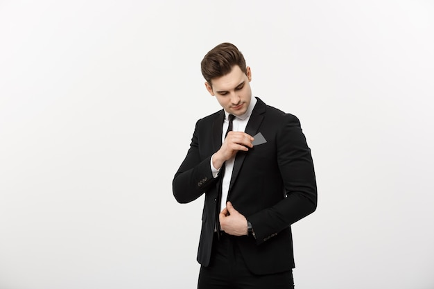 Business concept: businessman in black suit picking pasteboard or credit card out of pocket on gray background.