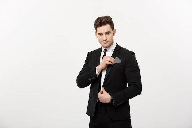 ビジネスコンセプト:灰色の背景のポケットからペーストボードまたはクレジットカードを選ぶ黒いスーツのビジネスマン。
