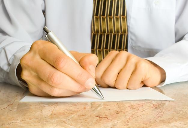 ビジネス コンセプト。ビジネスマンは空の紙にペンを書く