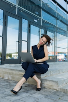 사업 개념. 사무실 건물의 입구의 배경에 대해 단계에 앉아 전화 통화와 노트북과 붉은 입술으로 근접 매력적인 젊은 비즈니스 여자