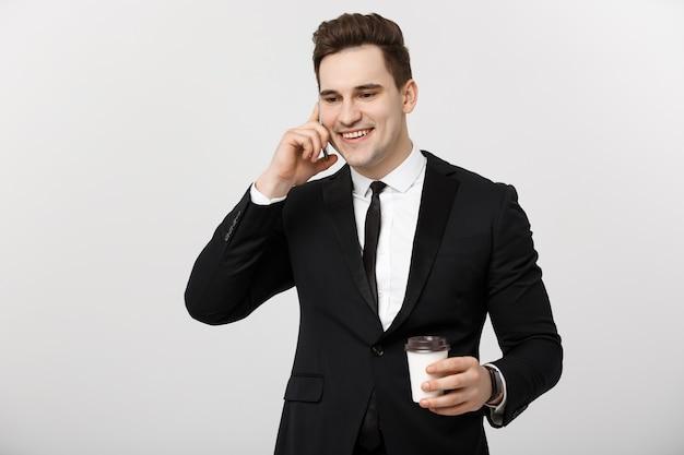 비즈니스 개념: 근접 촬영 자신감이 젊은 잘생긴 사업가 휴대 전화에 얘기 하 고 흰색 격리 된 배경 위에 커피를 마시는.