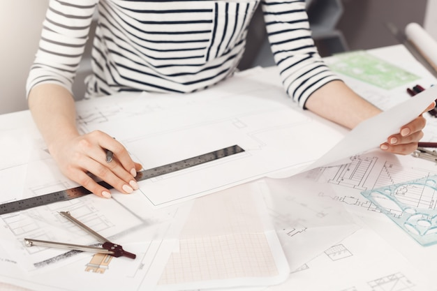Business concept. close up detail of young successful architect entrepreneur in striped clothes sitting at white table, looking through work plan, holding pen and ruler in hands, working in new busine