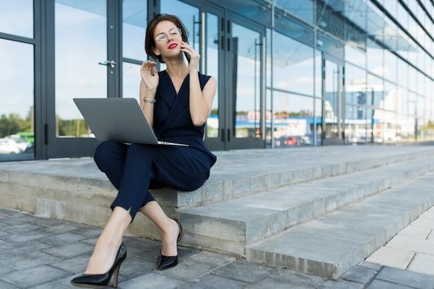 사업 개념. 사무실 건물의 벽에 단계에 앉아 노트북과 붉은 입술으로 매력적인 젊은 비즈니스 여자의 근접