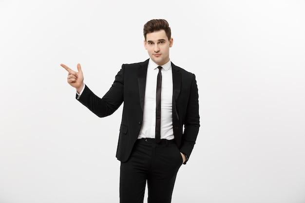 ビジネスコンセプト:白い背景の上に彼の指でコピースペースを指している若い成功したブルネテ株式市場のブローカーの男やビジネスマンの肖像画を閉じます。