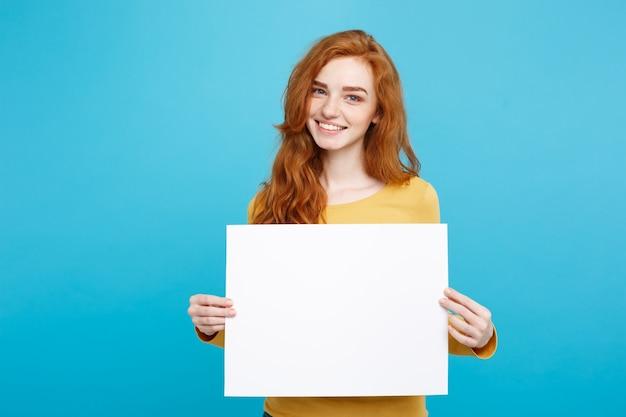 ビジネスコンセプト - クローズアップ肖像画若い美しい魅力的なジンジャー赤毛の女の子は、空白の看板を表示する笑顔青いパステルの背景。スペースをコピーします。