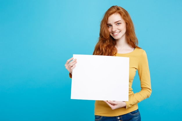 Business concept close up portrait young beautiful attractive ginger red hair girl smiling showing blank sign blue pastel wall copy space