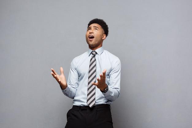 ビジネスコンセプト-灰色の壁に失望した表情で彼の前に手を示している自信を持って陽気な若いアフリカ系アメリカ人。