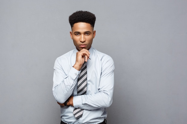 Business concept - confident thoughtful young african american holding hand on his chin and thinking about business.