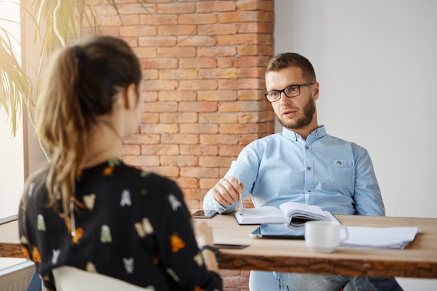 Business concept. dark-haired anonymous woman sitting at table in office in front of serious mature human resources manager, speaking about work responsibilities during job interview.